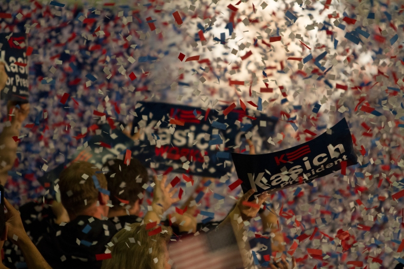 "Nikos Frazier | The Kent Stater A supporter holds a ""Kasich For President"" sign as confetti falls from the air at the Lou Higgins Recreation Center on Tuesday, March 15, 2016."